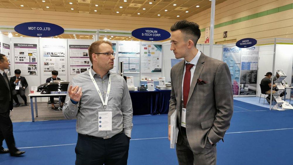 Malte Mund (l.), Projektmanager Internationalisierung an der Open Hybrid LabFactory, im Gespräch mit Henry Stonham, Messeorganisator der JEC Group.