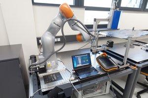 Freikinematisches Umformen am Versuchsstand zum robotergeführten Umfromen von thermoplastischen und faserverstärkten Formmassen.