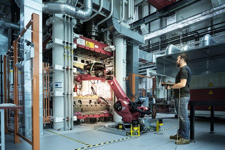 Im Infrarotofen oder Umluftofen vorgeheizte Halbzeuge können mit einem Sieben-Achs-Roboter aus dem Ofen entnommen und in das Werkzeug zur Weiterverarbeitung eingelegt werden.