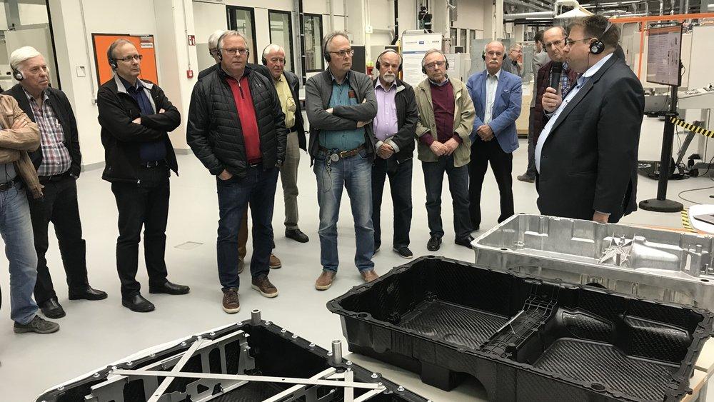 Dr.-Ing. Sierk Fiebig erläutert den VMA-Mitgliedern anhand unterschiedlicher Batteriegehäusewannen, wie durch die FVK-Metall-Hybridbauweise Gewicht bei der Bauteilfertigung eingespart werden kann.